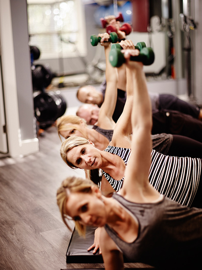 People lifting dumbells in a side plank